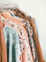 Kleidung in natürlichen Farben an einer Kleiderstange