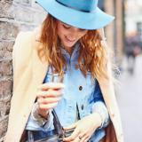 Eine Frau mit blauem Hut und beigen Mantel schaut in ihre schwarze Handtasche
