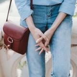 Eine Frau mit heller Kleidung und brauner Handtasche hält ihre Hände zusammen, man sieht nur die Hände und Beine