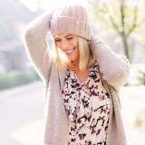Eine Frau in heller Kleidung hält ihre Hände am Kopf und lächelt