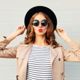 Eine Frau mit heller Kleidung, einem schwarzen Hut und einer runden Sonnenbrille, hält ihren Hut und formt mit den Lippen einen Kussmunde