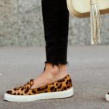 Blick auf die Füße einer Frau mit Schuhen in Leopardenoptik