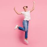 Eine Frau mit Jeans und hellem Oberteil vor einem rosa Hintergrund