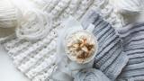 Ein Kaffee mit Sahne zwischen Wollknäulen und gestrickten Kleidungsstücken