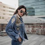Eine Frau mit Jeansjacke und Sonnenbrille steht vor einem großen Pavillion