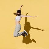 Eine Frau mit sportlicher Kleidung springt in die Luft vor einem gelben Hintergrund
