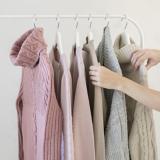 Zwei Hände gehen durch Wollpullover an einer Kleiderstange