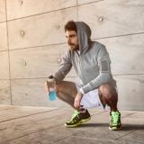 Ein Mann in Sportkleidung hockt vor einem Steinhintergrund und hält ein blaues Getränk in der Hand
