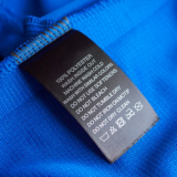 Pflegehinweisschild eines blauen Kleidungsstücks aus hundert Prozent Polyester