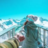 Eine Frau in Skikleidung hält eine Hand hinter sich und geht auf eine Aussichtsplattform in den Bergen