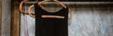 Ein ärmelloses schwarzes Kleid, das auf einem Kleiderbügel aus Holz hängt.