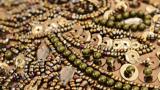 Nahaufnahme eines Kleidungsstücks mit vielen Pailletten und Perlen in Oliv- und Brauntönen.