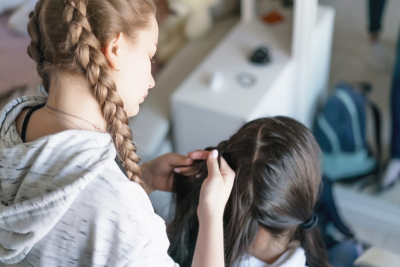A blonde girl with braided pigtails styling the hair of a girl with brown hair.