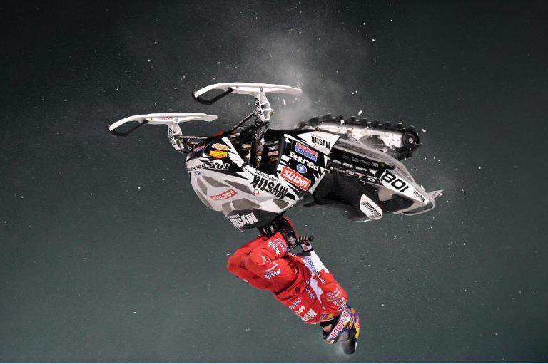 persona que realiza un giro en el aire pilotando una moto de nieve