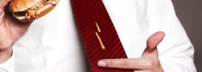 .Red striped tie with yellow sauce stain dripping from a burger
