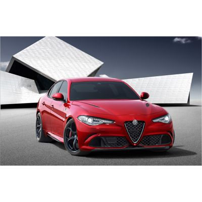 Red Alfa Romeo Giulia sedan with white geometric building in background