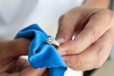 Reinigung Silberschmuck: Juwelier poliert Silberring mit Glitzerstein per Hand mit einem blauen Tuch