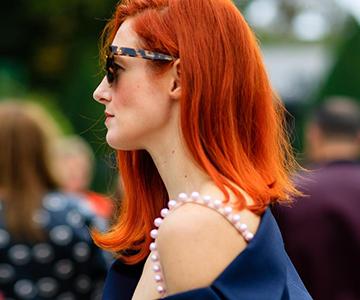 Frau mit roter Haarfarbe von der Seitenansicht während einer Feier