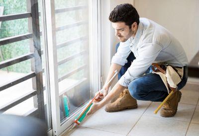 Un homme vêtu d'une chemise boutonnée rénovant l'extérieur d'une maison