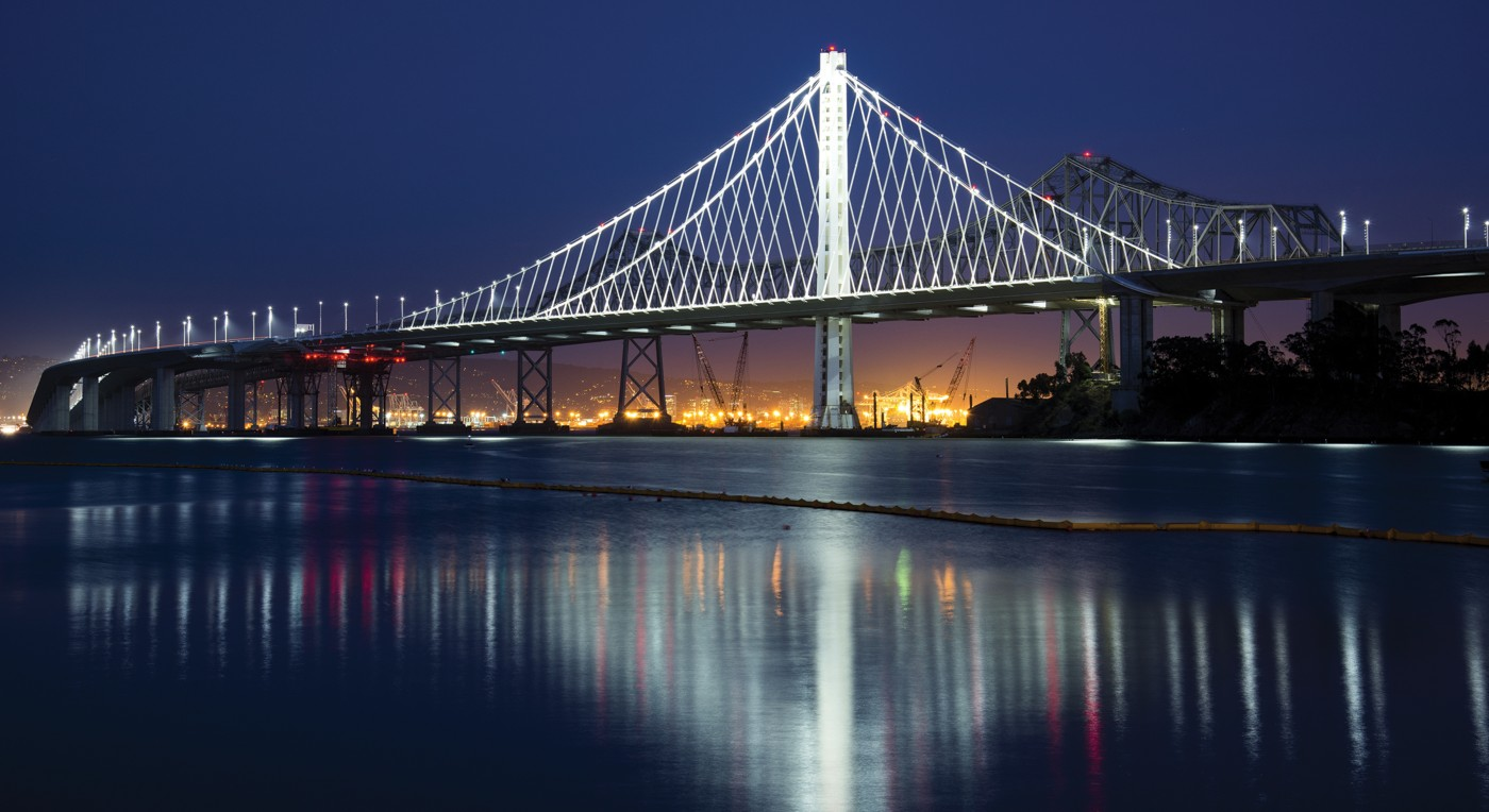 Photo of san francisco bay bridge at night with lights the bridge structure and the city lights in the background shutterstock ID 160570925