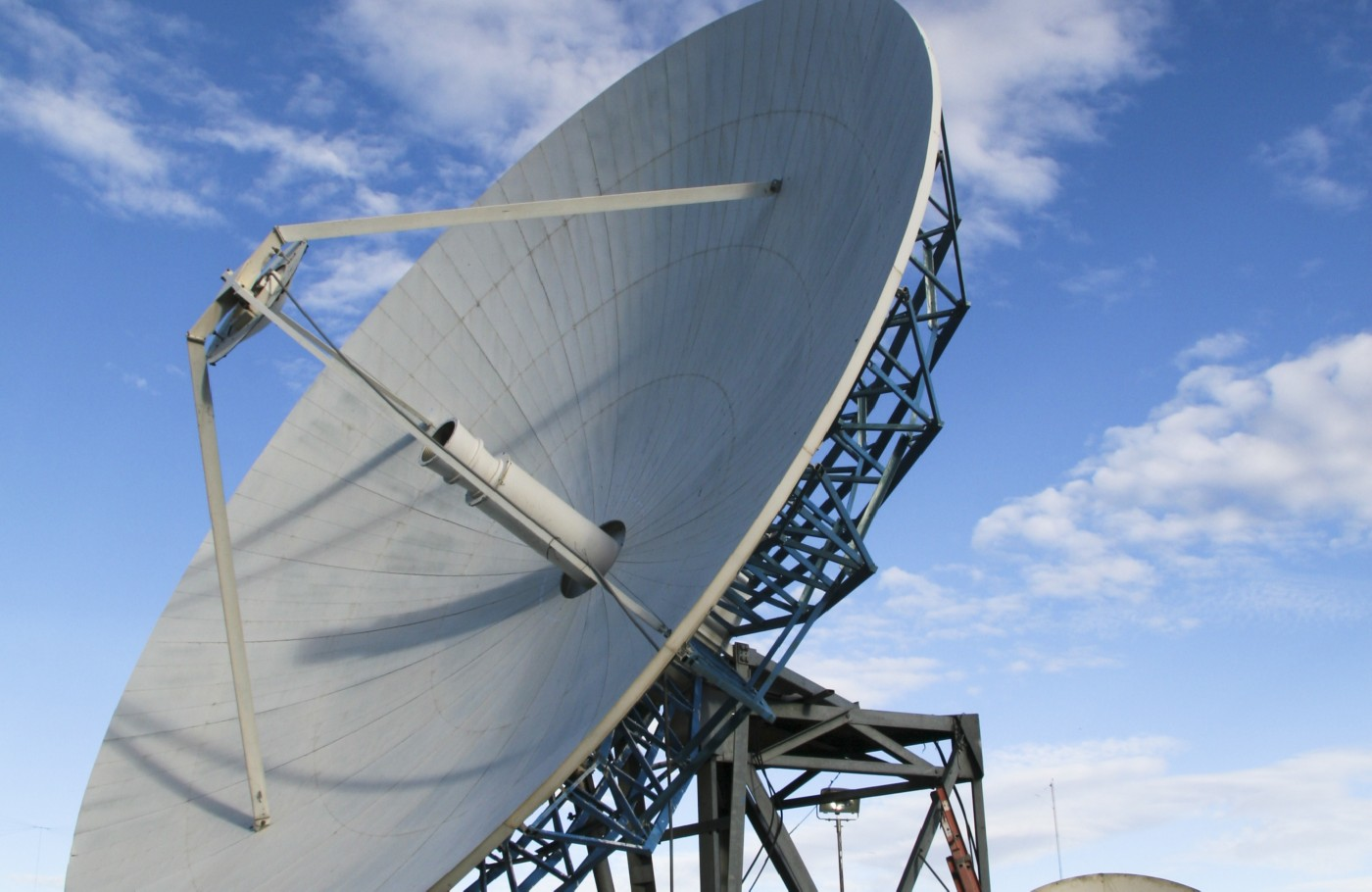 Photo of large grey satellite dish with blue sky and clouds in the background cropped shutterstock ID 22571947