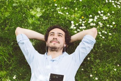 Relaxed man lying down at the meadow and listening to music