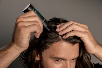 young man using Scalp Care MID tonic product for his long hair