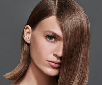 Frontansicht einer Frau mit brünettem, halblangem Haar und Seitenscheitel