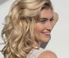 Blonde Frau lächelt und fasst sich durch ihre Lockenpracht