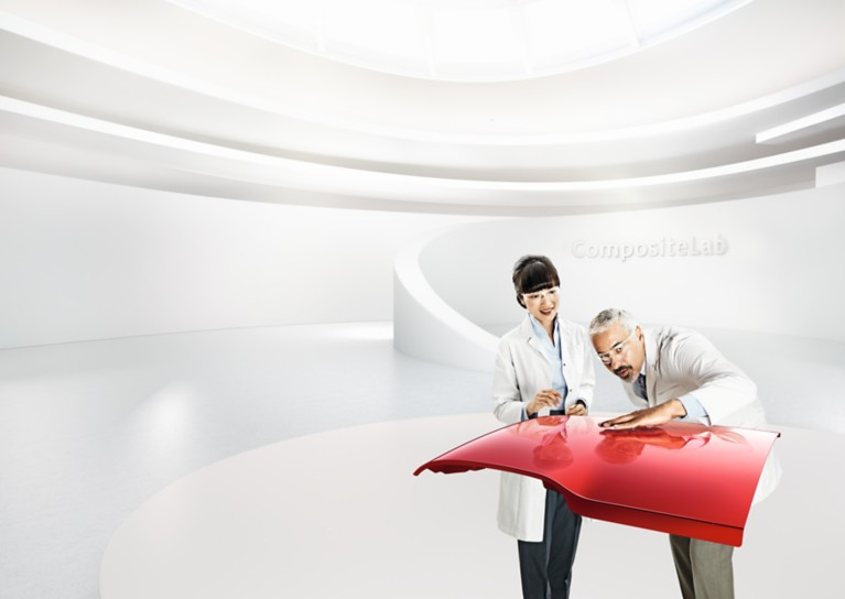 Two scientists examine the red roof panel of a roadster