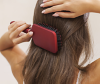 Woman brushing hair infront of a mirror