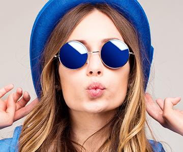 Frau mit langen Haaren trägt Hut und Sonnenbrille und macht einen Kussmund in die Kamera