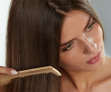Braunhaarige junge Frau beim Haare kämmen