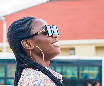 Zwei Frauen gehen lachend spazieren. Die schwarzhaarige Frau trägt ihren schwarzen Afro in langen Cornrows