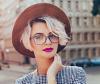 Blonde kurzhaarige Frau trägt Brille und Hut