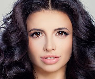 Frontansicht einer jungen Frau mit langen schwarzen und gelockten Haaren