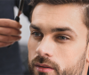 Brünetter Mann mit Sakko, Brille und nach oben gestyltem kurzem Haar mit einrasiertem Scheitel, der beginnende Geheimratsecken kaschiert