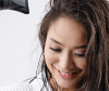 Frontansicht einer lächelnden Frau, die sich die Haare föhnt