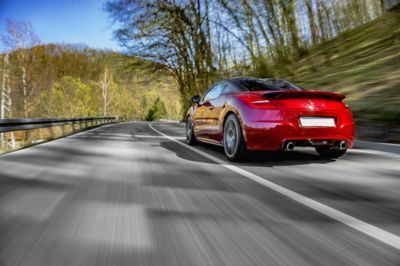 Red sports car driving on a double-sided road in nature