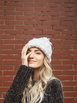 Woman with long scandi blonde hair and wearing a bobble hat