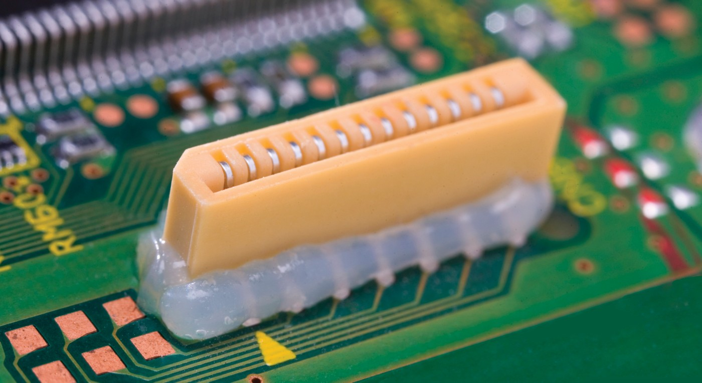 Photo of yellow connector on green pcb with loctite silicone encapsulant protecting and isolating the connector leads