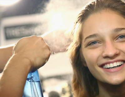 Hair stylist spraying hairspray on a girl's hair