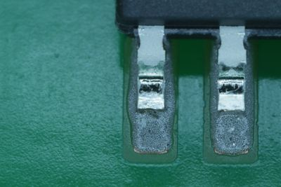 Closeup photo of SOIC small outline integrated circuit leads in wet solder paste