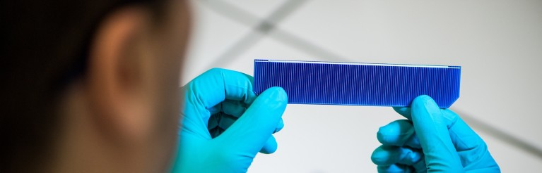 A scientist inspects a piece of solar paneling
