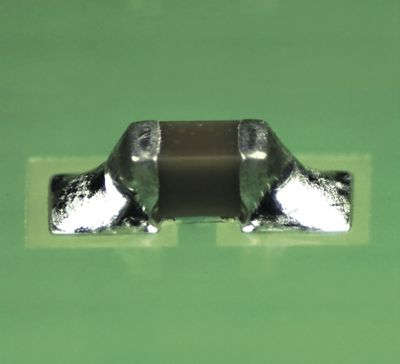 Closeup photo of component soldered onto a green pcb with lead free zero halogen temperature stable solder paste