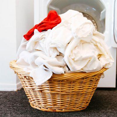 Tipps-Button zur Fleckenhilfe, links davon ein geflochtener Korb mit weißer Wäsche und einem roten Kleidungsstück.