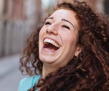 Braunhaarige Frau mit Naturlocken lacht herzlich