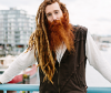 Man with red hair and dreadlocks leaning on a railing