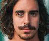 Braunhaariger Mann mit Bart und freiem Oberkörper trägt eine Surferfrisur