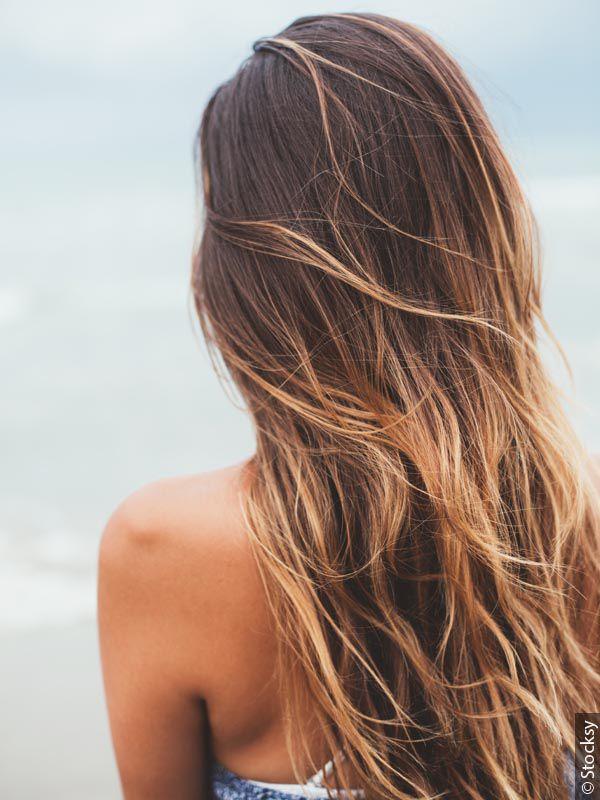 Donna vista da dietro con capelli castani e riflessi biondi